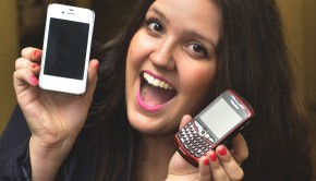 A young woman holds an iphone and BlackBerry