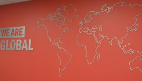 """An outline of a Word map is shown on a wall with the phrase """"we are global"""" to the left of it."""