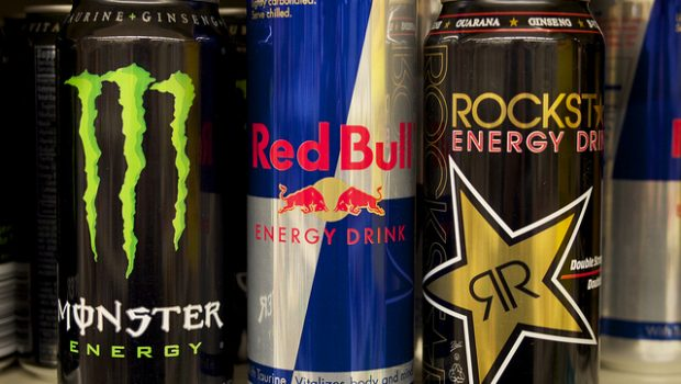 """A picture of energy drinks lined up in a commercial fridge, for sale. The drinks have colorful packaging.. and a few bottles clearly say """"caffeine,"""" and """"taurine,"""" two of the many ingredients that were heavily debated during the city hall meeting."""