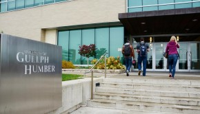 Three students walking into the entrance of University of Guelph-Humber