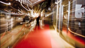 An artistic shot of a red carpet outside a theatre at night