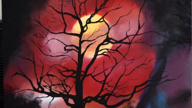 A naked tree stands alone under the moon surrounded by red skies.