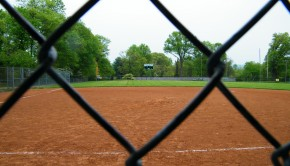 Looking through the fence onto an empty baseball field.