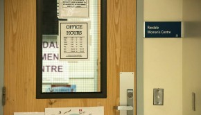 """A close-up of a wooden door is seen along with a portion of a sign reading """"Rexdale Women's Centre"""" read on a sign through the window on the door"""