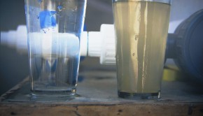 A glass of clean, clear and safe drinking water sitting on a table beside a glass of dirty, murky, unsafe drinking water.
