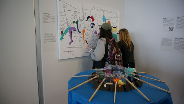 Two students paint colour onto a black and white illustration in the north humber gallery.